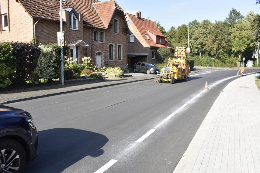 Eine Markierungsmaschine markiert einen Schutzstreifen auf einer Dorfstraße bei Warburg.