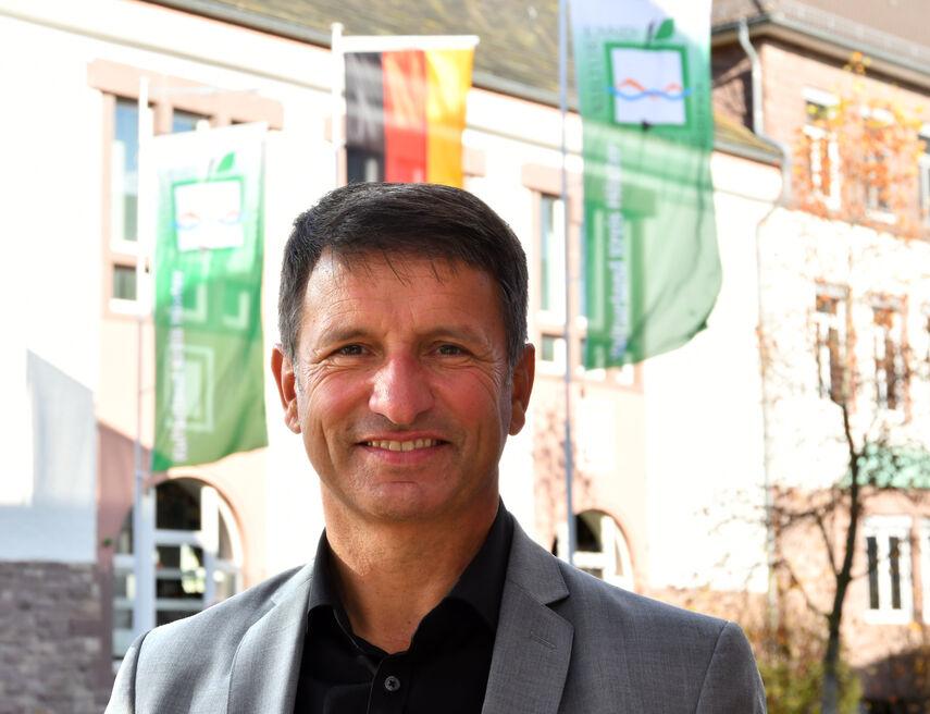 Landrat Michael Stickeln steht vor dem Kreisgebäude vor drei Flaggen.