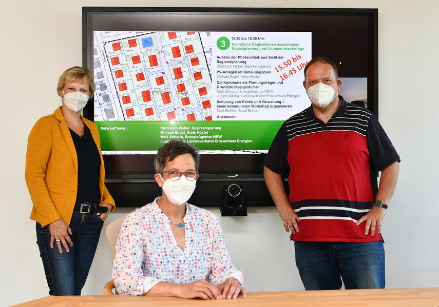 Dr. Kathrin Weiß, Martina Krog und Referent Michael Engel sitzen und stehen vor einem großen Bildschirm und stellen die Solaroffensive OWL vor.