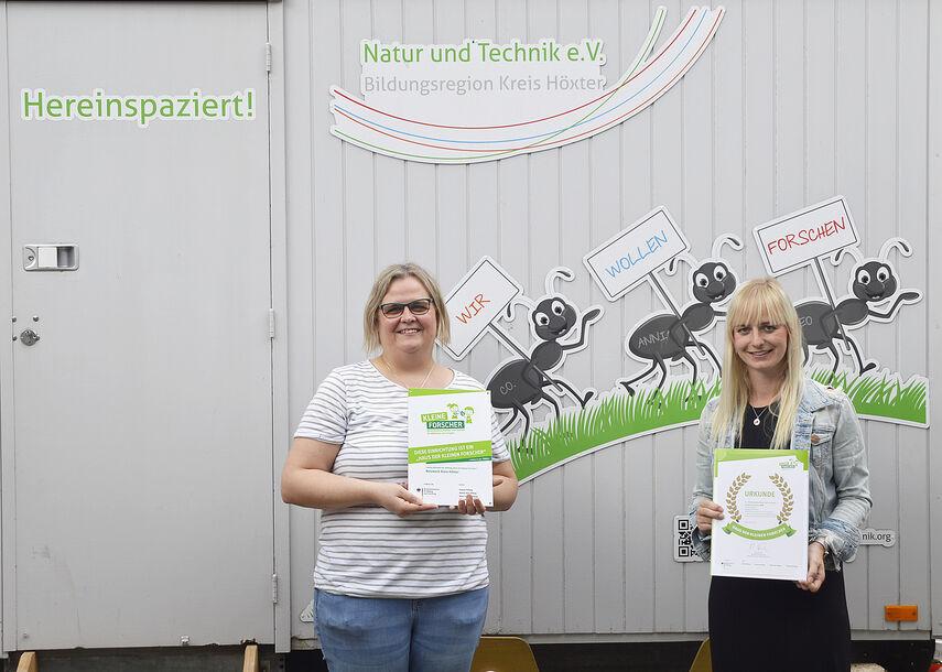 Anja Klatt und Sarah Mönnekes halten 2 Urkunden der Re-Zertifizierung in den Händen.