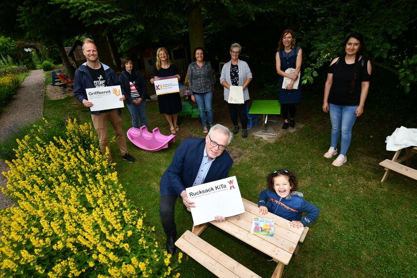 9 Personen stehen in einem Garten und bewerben die Förderprojekte des Kommunalen Integrationszentrums.