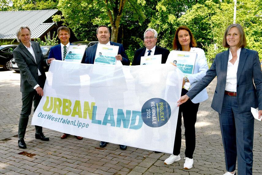 6 Personen halten einen Banner in der Hand mit der Aufschrift: 'Urban Land Ostwestfalen Lippe'.