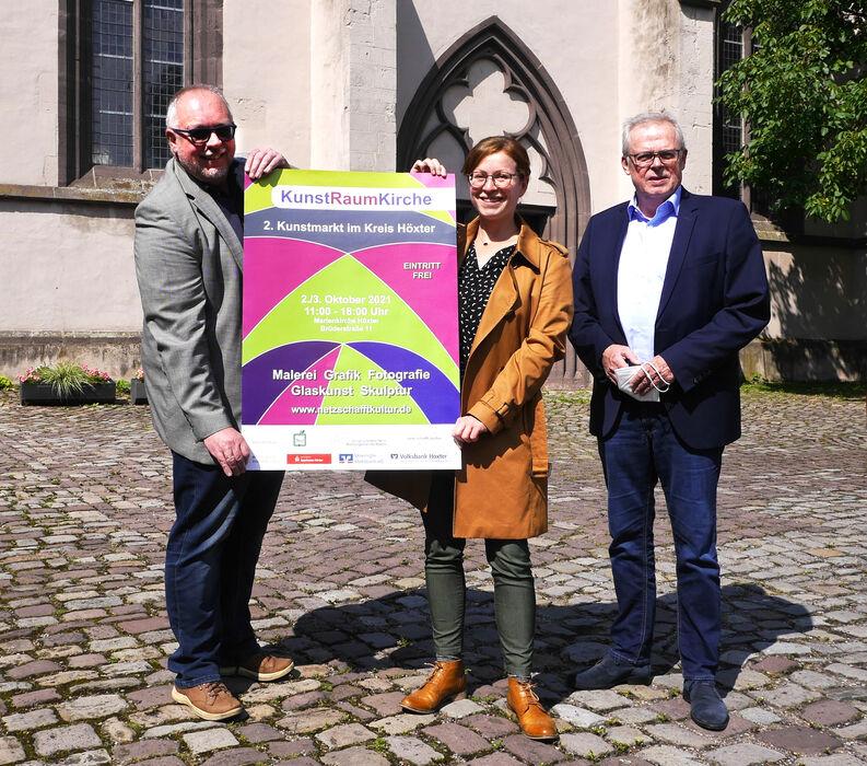 Pfarrer Uwe Neumann von der evangelischen Weser-Nethe-Kirchengemeinde, Kulturmanagerin Stephanie Koch und Kreisdirektor Klaus Schumacher präsentieren das Plakat für den 2. Kunstmarkt.