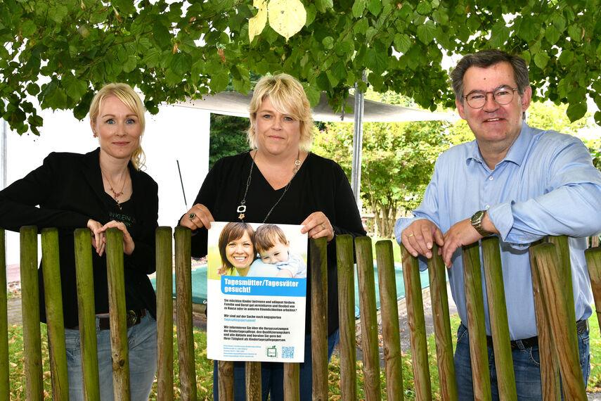 Stephanie Werk-Ferber, Christina Westermeier und Christian Rodemeyer werben für Tagesmütter/Tagesväter mit einem Plakat.