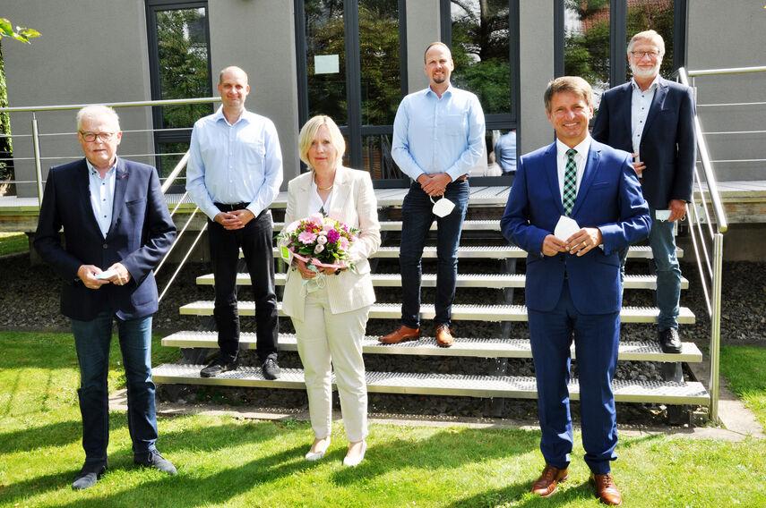 5 Personen stehen auf einer Treppe und verabschieden Ingrid Dreyer, die einen Blumenstrauß in den Händen hält.