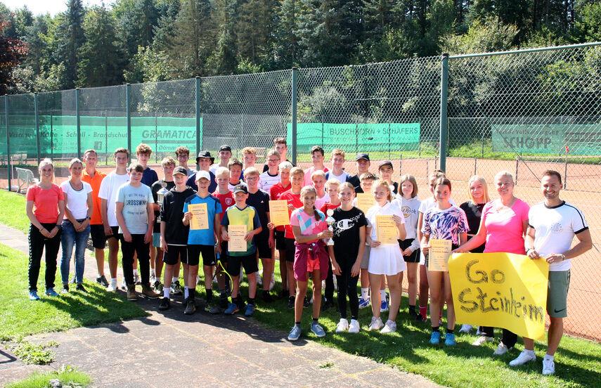 Eine große Gruppe von ca. 40 Spielern und Spielerinnen sowie Lehrkräften stehen vor einem Tennisplatz in Bad Driburg.