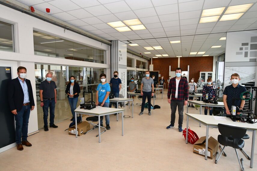 Schüler und Erwachsene stehen in einer Werkstatt.