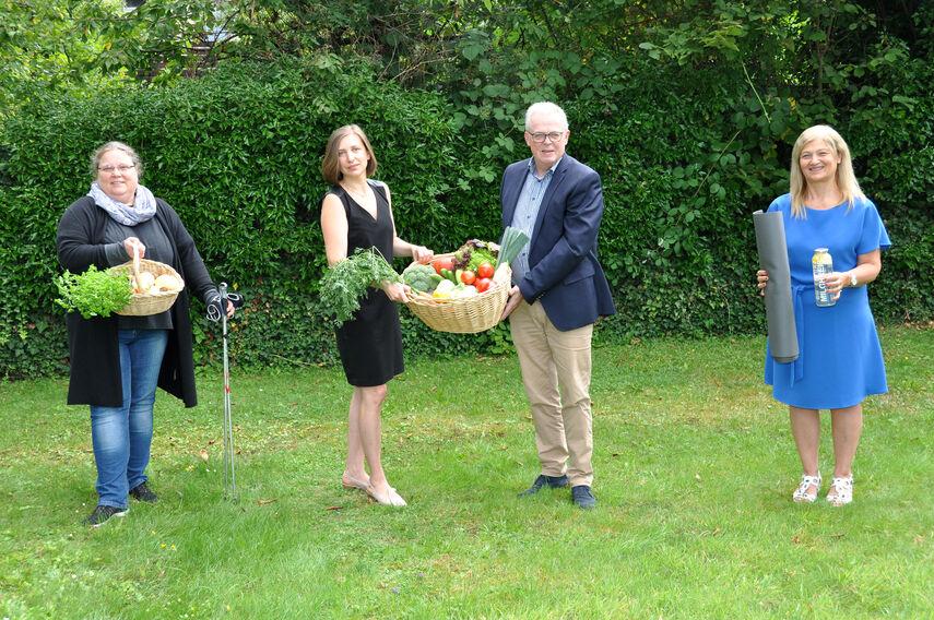 4 Personen werben für die Gesundheitskurse des KI. Zwei von ihnen halten einen Präsentkorb mit frischem Gemüse in den Händen.