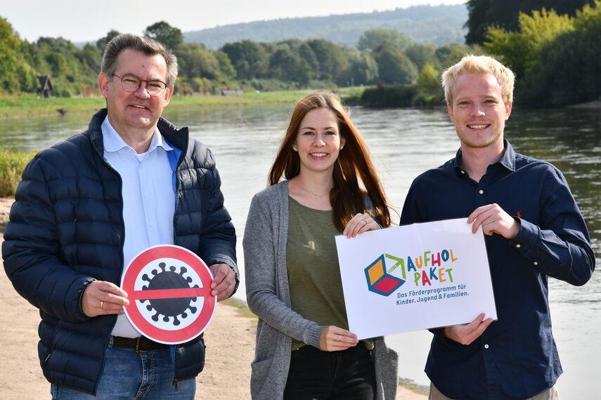 Christian Rodemeyer, Deborah Frischemeier und Rouven Speith stehen an der Weser in Höxter und stellen das 'Aufholpaket' vor.