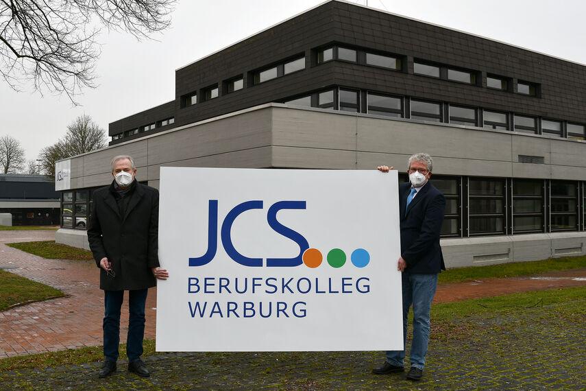 Kreisdirektor Klaus Schumacher und Schulleiter Matthias Gehle zeigen auf einem großen Schild das neue Logo des Johann-Conrad-Schlaun-Berufskollegs Warburg. Sie stehen mit dem Schild vor dem Berufskolleg in Warburg.