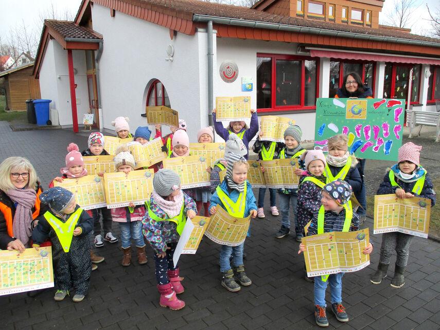 """Vorschlag hier: Im Bewegungskindergarten """"Kinderlobby"""" in Warburg-Menne halten mehrere Kinder und 2 Erzieherinnen den Stundenplan der Kindermeilen-Aktion in die Höhe."""