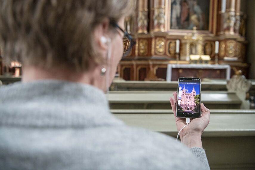 Eine Dame nutzt innerhalb der Corveyer Kirche eine App per Smartphone, um sich eine von acht Hörgeschichten anzuhören.