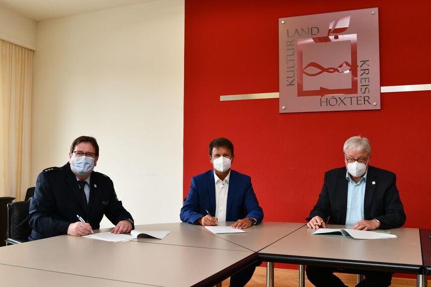 Christian Brenski, Landrat Michael Stickeln und Klaus Brune unterschreiben an einem Tisch die Kooperationsvereinbarung