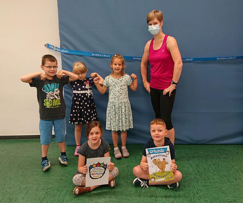 Die Kursleiterin Petra Koch steht mit 5 Kindern in einer Turnhalle. Die Kinder halten die Urkunde 'Bärenstark' in der Hand.