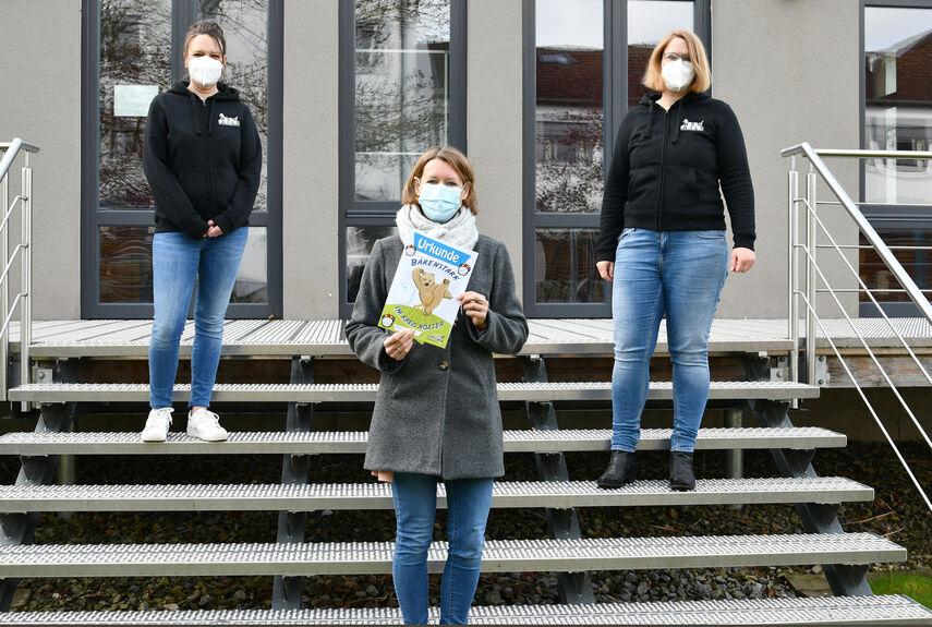Petra Huppert Buch, Silke Merkel und Sandra Wegener stehen auf einer Treppe und zeigen eine Urkunde vom Programm 'Bärenstark'.