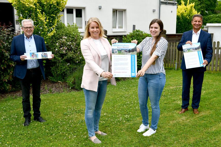 Klaus Schumacher, Katharina Serinelli, Dorina Bernsmann und Landrat Michael Stickeln halten ein Plakat für den Heimatpreis in der Hand.