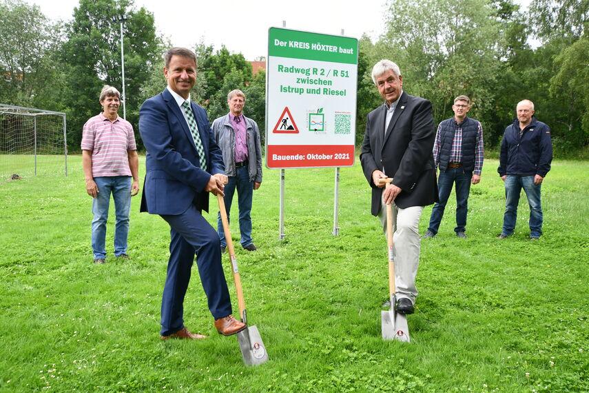 6 Personen stehen auf einer Wiese. Ein Schild weißt darauf hin, dass der Kreis Höxter einen einen neuen Radweg baut bis Oktober 2021. Landrat Michael Stickeln und Bürgermeister Hermann Temme halten einen Spaten in der Hand.